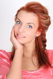 Beautiful red-haired woman in pink smiling Stock Photo