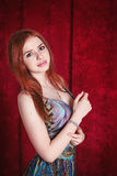 Beautiful red-haired woman. Portrait of beautiful red-haired woman in colorful dress standing against red curtain Royalty Free Stock Photography