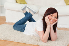 Beautiful red-haired woman posing. While lying on a carpet in the living room Stock Photography