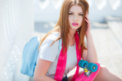 Beautiful red-haired woman posing with a skateboard Stock Photography