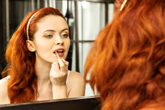 Beautiful red-haired woman with red lipstick in front of mirror in bathroom. Makeup concept Stock Image