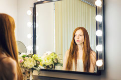 Beautiful red-haired woman sitting in front of a mirror Royalty Free Stock Photo