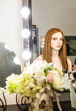 Beautiful red-haired woman sitting in front of a mirror Royalty Free Stock Photos