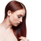 Beautiful red haired woman touching hair Stock Images