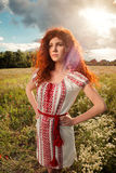 Beautiful red haired woman in Ukrainian national dress. Beautiful red haired woman with sunset back-light in Ukrainian national dress Royalty Free Stock Photography