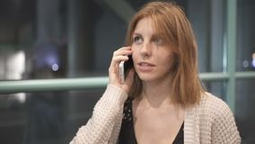 Beautiful red-haired woman using smart phone technology in city streets at night. Beautiful red-haired woman using smart phone technology in city stock footage