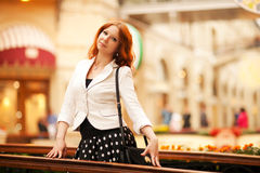 Beautiful red-haired woman. Walking in the mall Royalty Free Stock Photography