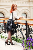 Beautiful red-haired woman. Walking in the mall Royalty Free Stock Image