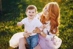 Mom and son. Beautiful red-haired women with her wonderful son on a summer park Stock Images