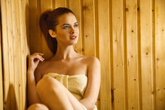 Beautiful red-haired young woman relaxing in a finnish sauna Royalty Free Stock Photo