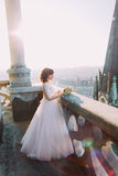Beautiful red-head bride posing with bouquet on old castle balcony, cityscape background Royalty Free Stock Image