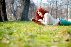 Beautiful red head young woman reading book Royalty Free Stock Photography