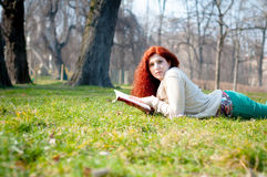 Beautiful red head young woman reading book Royalty Free Stock Image