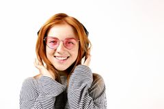 Beautiful red headed young woman posing, showing emotional facial expressions and making funny faces, dancing with big headphones. Young attractive natural stock image