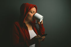Beautiful red hooded woman drinking coffee and sending text mess Stock Photography