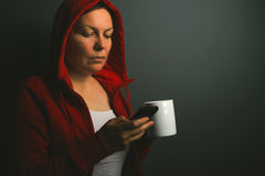 Beautiful red hooded woman drinking coffee and sending text mess Royalty Free Stock Image
