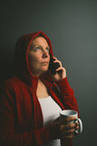 Beautiful red hooded woman drinking coffee and using mobile phon Royalty Free Stock Image
