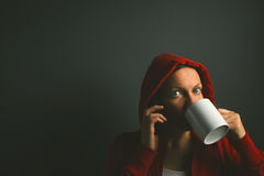 Beautiful red hooded woman drinking coffee and using mobile phon Stock Images