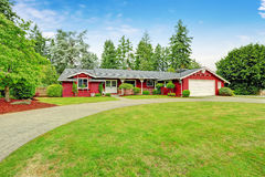 Beautiful red house with garage and curb appeal. Beautiful red American classic farm house with chuge green lawn. View of entrance porch with walkway and garage Stock Image
