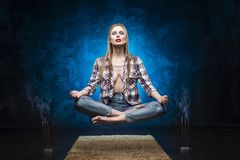 Beautiful red lips blonde big breast girl wearing an unbuttoned. Shirt and jeans meditates and levitates over the floor near smoky aromatic sticks. Copy space Stock Photo