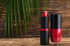 Beautiful red lipstick and nail polish on a wooden background, on the left place for your lettering stock image
