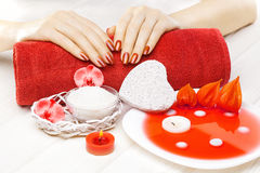 Beautiful red manicure with red orchid flower and towel on the white wooden table. Royalty Free Stock Photography