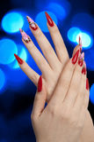 Beautiful red nails and blue lights. Girl fingers with beautiful drawing on nails over abstract spots of blue lights royalty free stock images