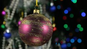 Beautiful red New Year and Christmas decoration ball swinging on rope. Against a background of a rotating Christmas tree and a flashing garland stock footage