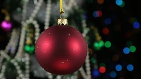 Beautiful red New Year and Christmas decoration ball swinging on rope. Against a background of a rotating Christmas tree and a flashing garland stock video footage