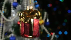 Beautiful red New Year and Christmas decorations in the form of a gift swinging on a rope. Against a background of a rotating Christmas tree and a flashing stock footage