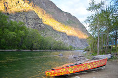 A beautiful red painted boat on a mountain river beach at sunset Stock Photography