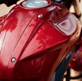 A petrol tank of a stylish motorbike unique stock photo. A beautiful red petrol tank of a motorbike isolated unique metallic background stock photo royalty free stock image