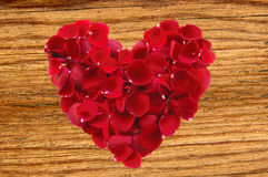 Beautiful red rose petals as heartsymbol on wooden Stock Photography