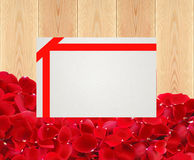 Beautiful red rose petals and card on wooden planks texture Stock Photo