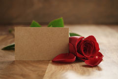 Beautiful red rose with petals and empty paper card on old wood table Royalty Free Stock Photos