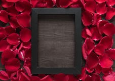 Beautiful red rose petals and frame picture are on the wooden ba Stock Photo