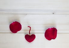 Beautiful red rose petals and red heart on wooden background  Royalty Free Stock Images