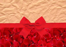 Beautiful red rose petals and red ribbon with bow over old paper Stock Photography