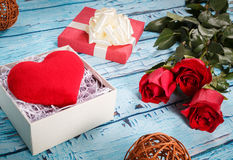 Beautiful red roses and heart sweetheart as a gift on a blue background. Royalty Free Stock Image