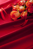 Beautiful red roses on the red satin Stock Image