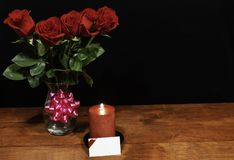 Beautiful red roses in vase with pink bow and red candle on wooden table on dark background stock images