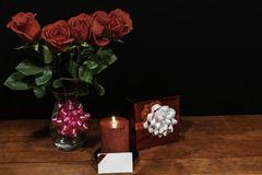 Beautiful red roses in vase with pink bow wrapped present and red candle with name tag on wooden table on dark background stock photo