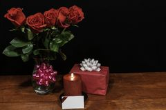 Beautiful red roses in vase with pink bow wrapped present and red candle with name tag on wooden table on dark background royalty free stock photo