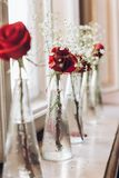 Beautiful red roses and white baby breath in glass vases on tabl Stock Images