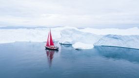 Beautiful red sailboat next to a massive iceberg. royalty free stock image