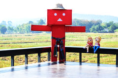 Beautiful red scarecrow. Scarecrow on the terrace with the backdrop of the field Stock Photos