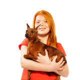Beautiful red smiling girl with dog on her hands Royalty Free Stock Photography