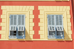Beautiful red stucco house with two blue traditional french shutter windows in Nice, France. Royalty Free Stock Photo
