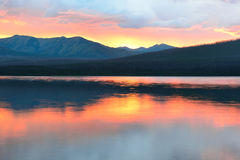 Beautiful red sunset into the Mountains and McDonald lake in Glacier National Park Stock Photography