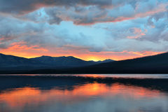Beautiful red sunset into the Mountains and McDonald lake in Glacier National Park Royalty Free Stock Photography
